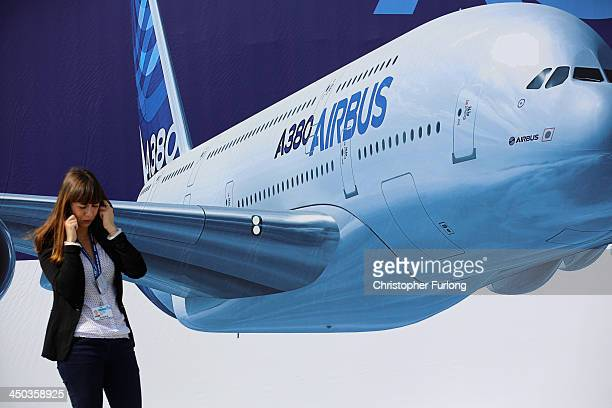 A delegate talks on her phone next to a poster of an Airbus A380 during the Dubai Airshow on November 18 2013 in Dubai United Arab Emirates The Dubai...