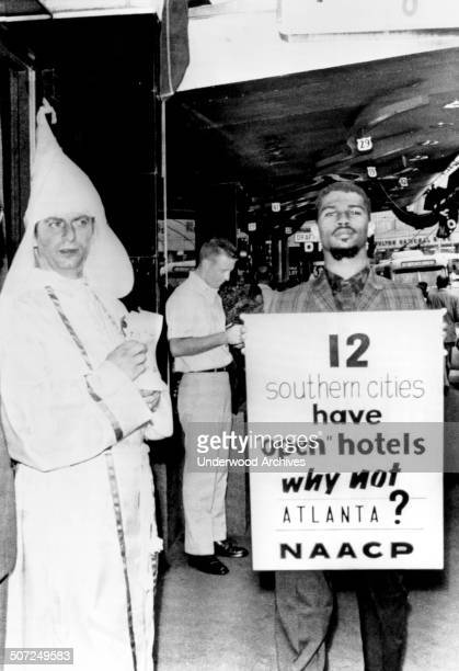 A delegate to the NAACP convention pickets in front of a downtown hotel protesting its segregation policy while a member of the Ku Klux Klan hands...