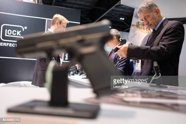 A delegate tries out a handgun on the Glock display stand at the DSEI event at the ExCel centre on September 12 2017 in London England The annual...