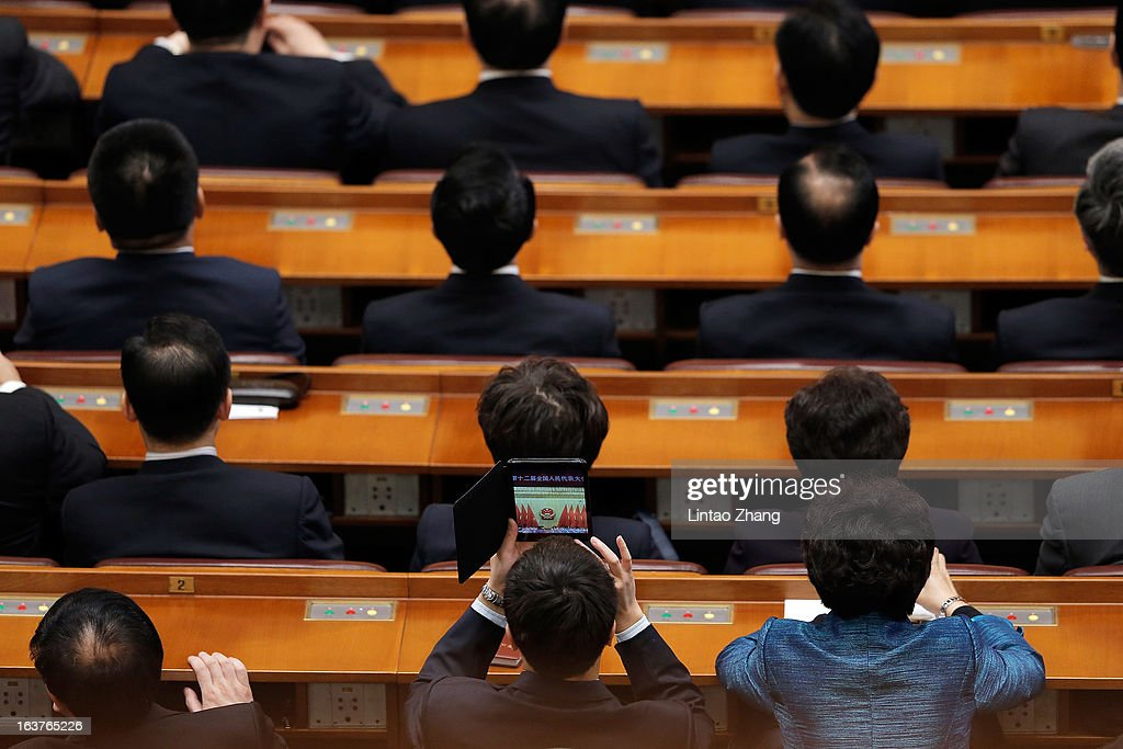 A Delegate uses an Apple Mini to take a picture during the fifth plenary meeting of the National People's Congress at the Great Hall of the People on March 15, 2013 in Beijing, China.Li Keqiang was elected as China's Premier Friday at the 12th National People's Congress, the country's top legislature.