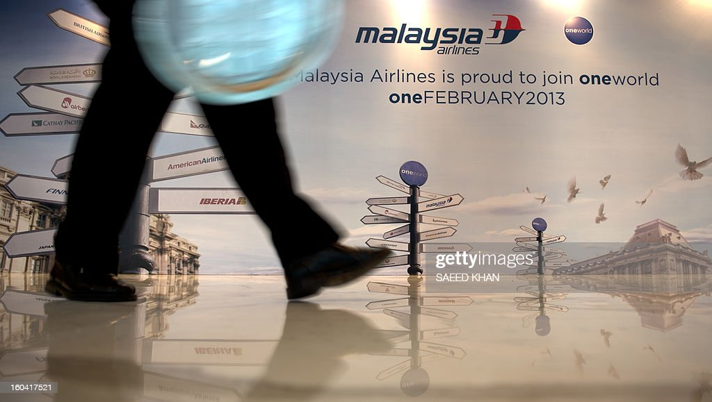 A delegate walks in front of a billboard advertising Malaysia Airlines Group's alliance with Oneworld Alliance in Kuala Lumpur on January 31, 2013 before Malaysia Airlines becomes part of Oneworld Alliance at midnight Kuala Lumpur time. The airline said its addition will expand the Oneworld coverage to over 840 destinations in 155 countries. PHOTO / SAEED