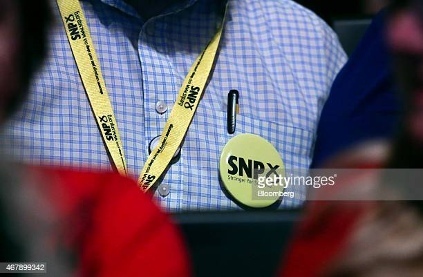 A delegate wears a Scottish National Party badge at the party's Spring Conference event in Glasgow UK on Saturday March 28 2015 Polls show the SNP...