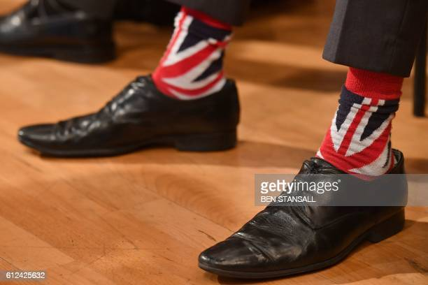 A delegate wears Union flag themed socks as he listens to a keynote address on the third day of the annual Conservative Party conference at the...