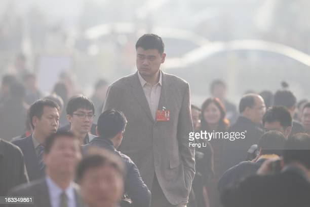 Delegate Yao Ming a former NBA basketball star walks from Tiananmen Square to the Great Hall of the People to attend a plenary session of the Chinese...