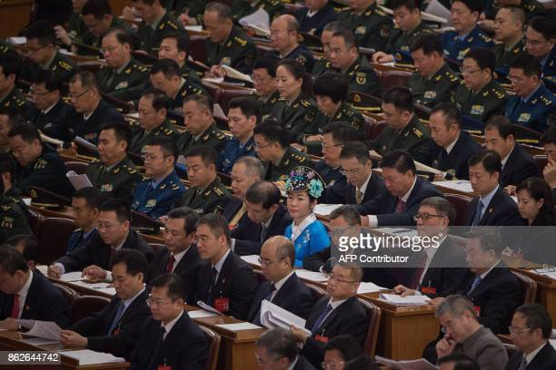 Delegates and a delegate wearing an ethnic minority outfit listen to Chinese President Xi Jinping's address at the opening of the 19th Communist...