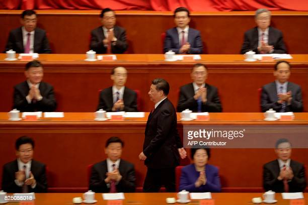 TOPSHOT Delegates applaud as China's President Xi Jinping makes his way to the podium to deliver a speech at a ceremony to commemorate the 90th...