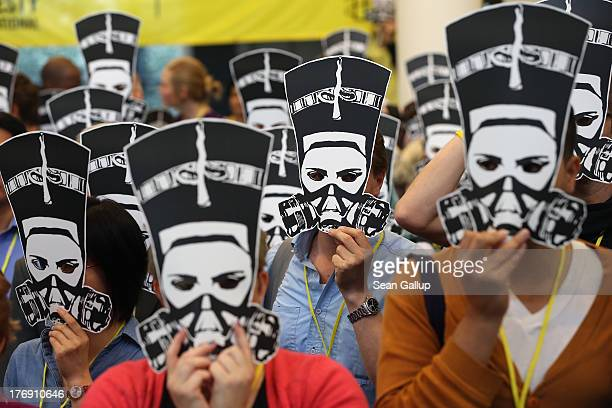 Delegates at a meeting of Amnesty International hold up masks depicting ancient Egyptian Queen Nefertiti wearing a gas mask in protest against the...