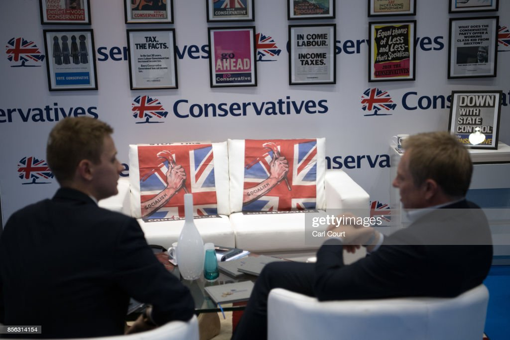 Delegates chat next to cushions mocking socialism as they attend the first day of the annual Conservative Party conference on October 1, 2017 in Manchester, England. Theresa May has targeted young voters pledging help on student fees and housing as the Conservatives gather in Manchester for their annual party conference, amid reports of growing Cabinet divisions over the Brexit strategy.