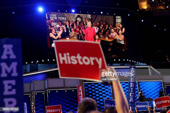 Delegates cheer as a screen displays Democratic presidential candidate Hillary Clinton delivering remarks to the crowd during the evening session on...