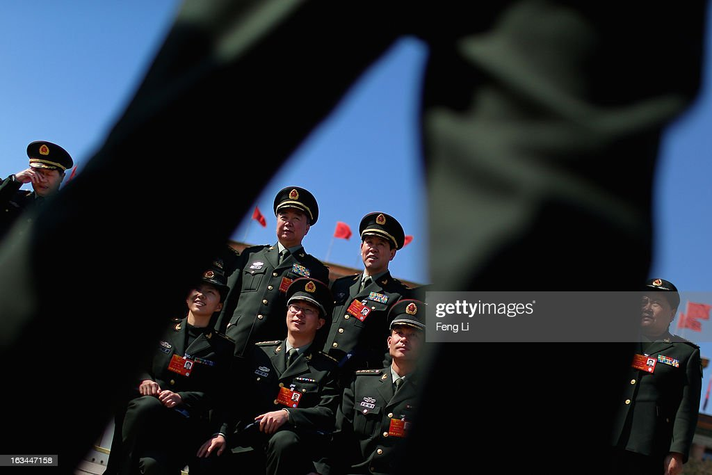 Delegates from Chinese People's Liberation Army pose for photos outside the Great Hall of the People after attending a plenary session of the National People's Congress on March 10, 2013 in Beijing, China. The State Council, China's cabinet, will begin its seventh restructuring attempt in the past three decades to roll back red tape and reduce administrative intervention. Several departments under the State Council will be reorganized according to a plan on the institutional restructuring and functional transformation of the State Council, which was submitted to the plenary session of the National People's Congress Sunday.