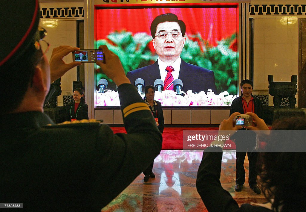 Delegates have their picture taken in front of a large screen televising Chinese President Hu Jintao's speech at the opening session of the ruling Communist Party's five-yearly congress, 15 October 2007, at the Great Hall of the People in Beijing. Hu opened China's biggest political event with pledges to curb the worst excesses of breakneck economic growth and implement cautious political reforms while addressing the ruling Communist Party's elite, gathered for their five-yearly Congress, with Hu acknowledging that China's modernisation drive since the late 1970s had also caused huge environmental and social problems. AFP PHOTO/Frederic J. BROWN