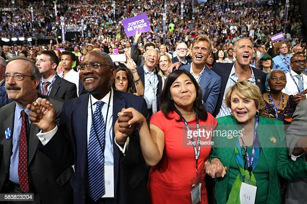 Delegates hold hands during the evening session of the third day of the Democratic National Convention at the Wells Fargo Center July 27 2016 in...