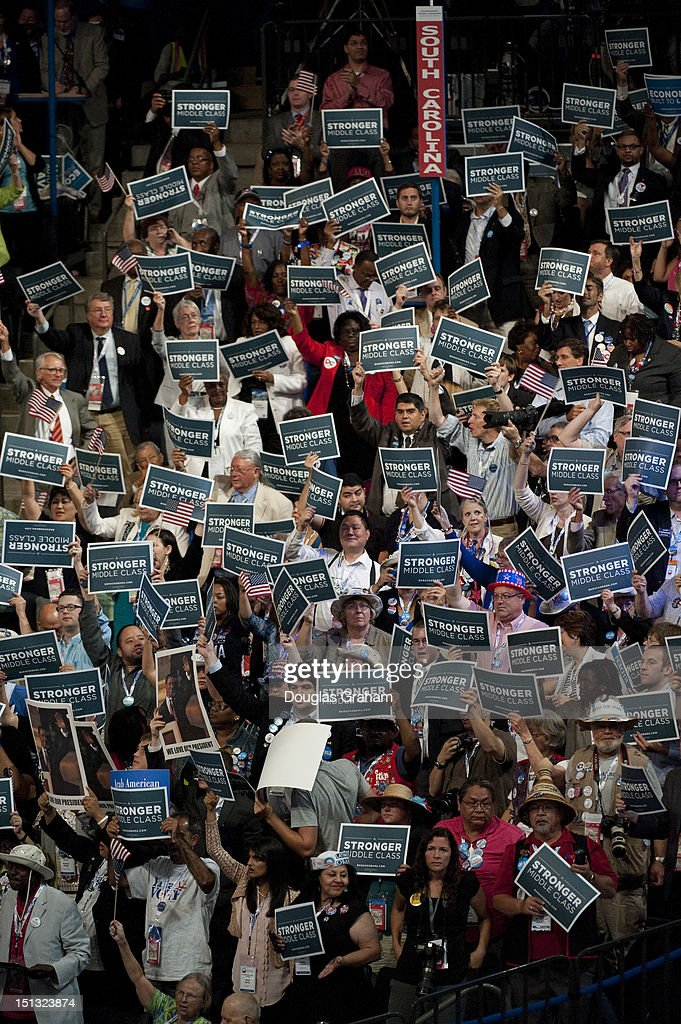 Delegate's hold up signs as Former President Bill Clinton addresses the crowd at the Democratic National Convention in the Time Warner Cable Arena in...