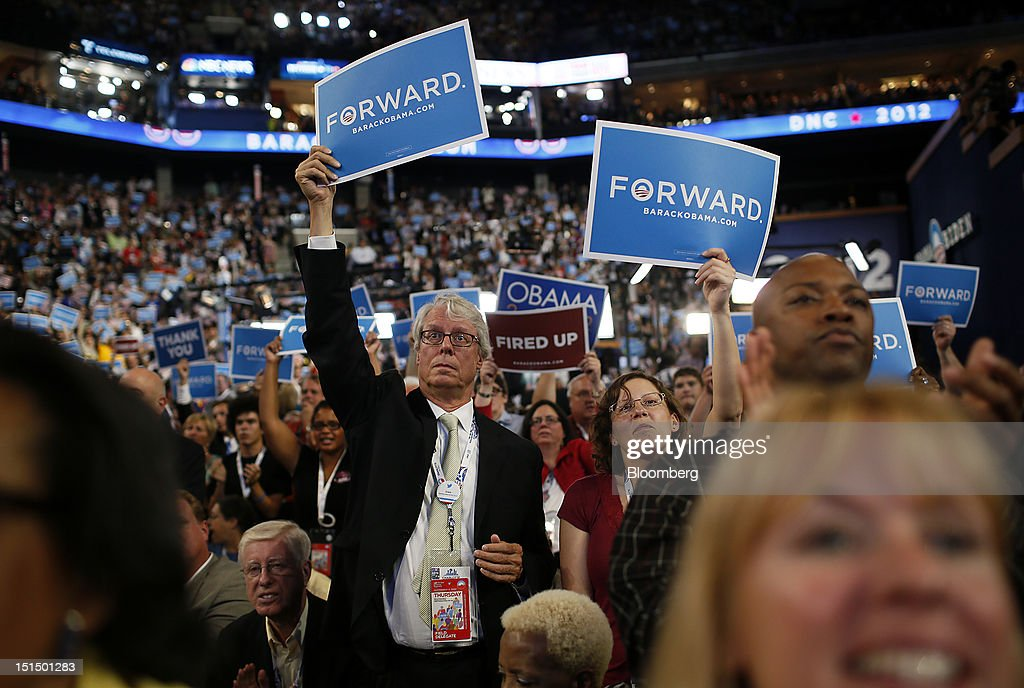 Delegates hold up signs while listening to U.S. President Barack Obama, unseen, speak during day three of the Democratic National Convention (DNC) in Charlotte, North Carolina, U.S., on Thursday, Sept. 6, 2012. President Barack Obama's prime-time nomination acceptance speech tonight at the DNC is aimed at convincing voters that a slow economic recovery will accelerate if they give him a second term. Photographer: Victor J. Blue/Bloomberg via Getty Images