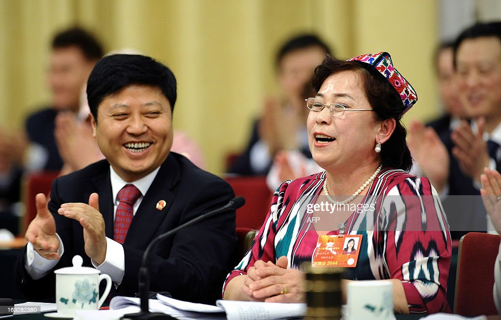 A delegates (R) laughs after her speech during the Xinjiang Uygur Autonomous Region opening session as part of the National People's Congress (NPC) in Beijing on March 7, 2013. Thousands of delegates from across China were meeting this week to seal a power transfer to new leaders whose first months running the Communist Party have pumped up expectations with a deluge of propaganda.