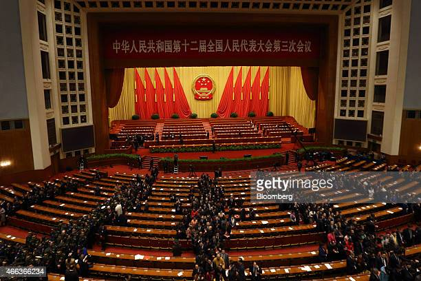 Delegates leave after the closing session of the third session of the 12th National People's Congress at the Great Hall of the People in Beijing...