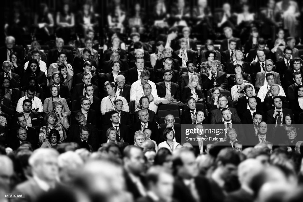 Delegates listen to Chancellor of the Exchequer George Osborne deliver his speech in the main hall on the second day of the Conservative Party...