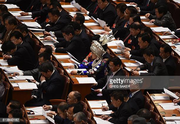 Delegates listen to Chinese Premier Li Keqiang's work report during the opening session of the National People's Congress in the Great Hall of the...