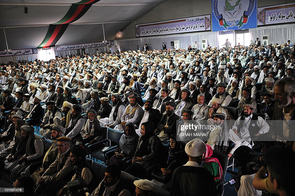 Delegates look on as Afghan President Hamid Karzai delivers a speech to the National Consultive Peace Jirga in Kabul on June 2, 2010. The Taliban claimed responsibility for a series of attacks on a landmark gathering in the Afghan capital, where hundreds of delegates are meeting to discuss peace talks. 'We have four suicide attackers placed on the top of a tall building near the jirga tent. They are threatening the jirga tent,' Zabihullah Mujahid, a Taliban spokesman, told AFP by telephone.AFP PHOTO/SHAH Marai