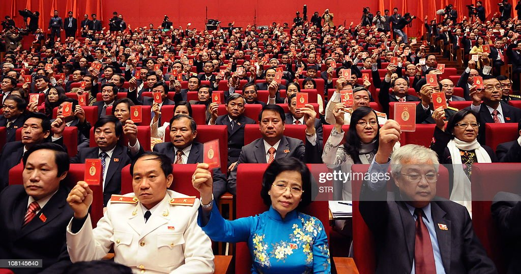 Delegates of the current 11th national congress of Vietnam Communist Party raise their red membership cards to vote in the congress' final resolution...
