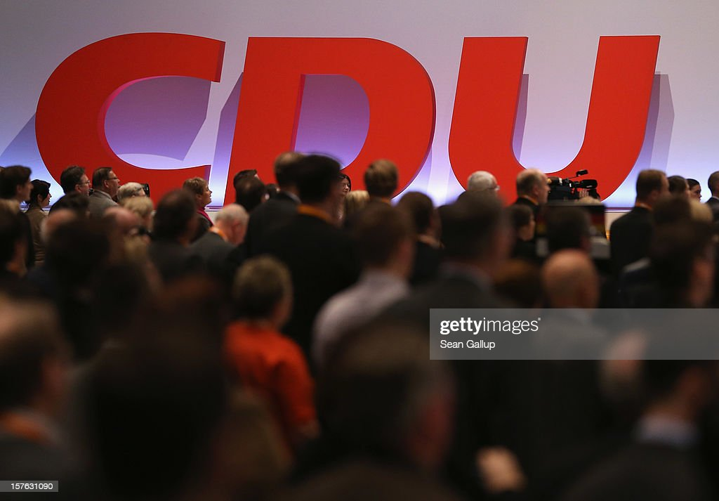 Delegates of the German Christian Democratic Union sing the national anthem as the CDU logo stands behind at the conclusion of the CDU federal party...