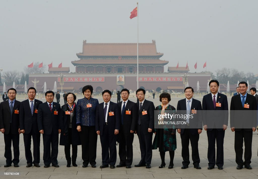 Delegates pose for photos in Tiananmen Square before the elections of the new vice premiers, foreign and defense ministers of China during the 12th National People's Congress (NPC) in the Great Hall of the People in Beijing on March 16, 2013. China's parliament named Xi Jinping as president on March 15 four months after he took charge of the Communist Party with pledges of reform that have raised hopes but so far yielded little change. AFP PHOTO / Mark RALSTON