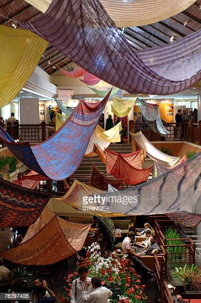Delegates rest under decorations of batiks clothings at the UN Climate Change Conference 2007 venue in Nusa Dua on Bali island 07 December 2007 In...