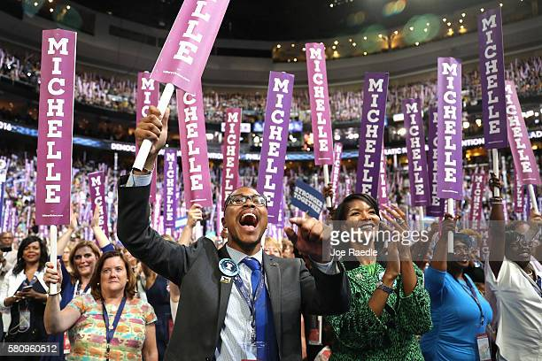 Delegates stand and cheer as first lady Michelle Obama delivers remarks on the first day of the Democratic National Convention at the Wells Fargo...