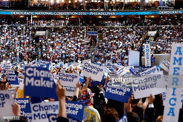 Delegates stand and cheer as former US President Bill Clinton delivers remarks on the second day of the Democratic National Convention at the Wells...
