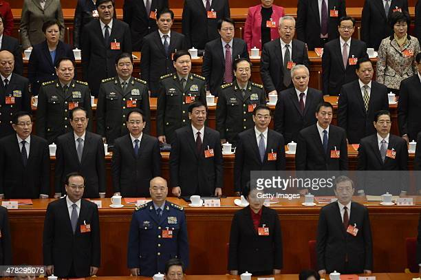 Delegates stand for the national anthem during the closing ceremony of the second session of 13th National People's Congress at the Great Hall of the...