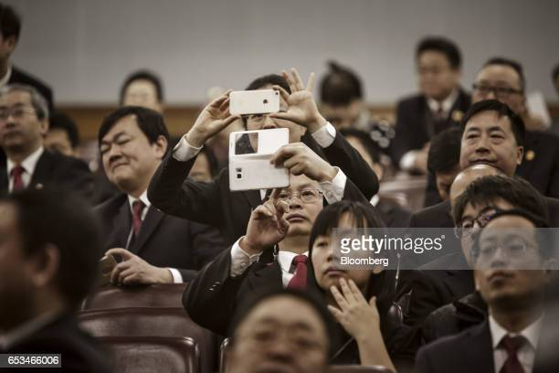 Delegates take photos with their smartphones during the closing ceremony of the National People's Congress in Beijing China on Wednesday March 15...
