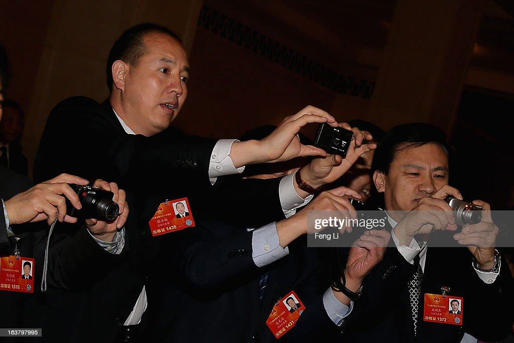 Delegates takes photos as they arriving the sixth plenary meeting of the National People's Congress at the Great Hall of the People on March 16, 2013 in Beijing, China. The new lineup of China's State Council, nominated by Premier Li Keqiang, was endorsed by lawmakers at the ongoing national legislative session Saturday afternoon.