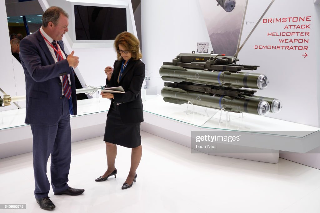 Delegates talk as they stand near a missile system on the 'MBDA' display area at the DSEI event at the ExCel centre on September 12, 2017 in London, England. The annual weapons and security trade fair sees manufacturers of all aspects of military, naval, airforce and security from all over the world display their latest designs to delegates.
