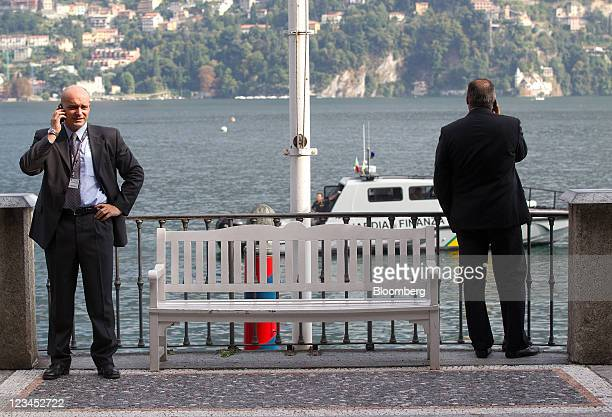 Delegates talks on their mobile phones by the edge of Lake Como during a break in sessions at the Ambrosetti Workshop in Cernobbio near Como Italy on...