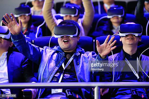 Delegates try a roller coaster ride using Gear VR headsets manufactured by Samsung Electronics Co at the Mobile World Congress in Barcelona Spain on...
