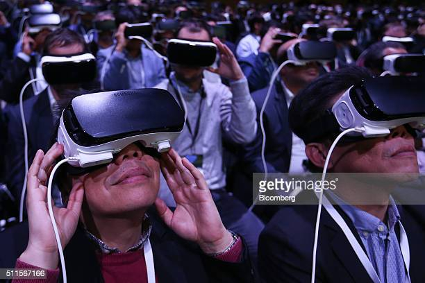 Delegates use Gear VR headsets manufactured by Samsung Electronics Co at the Samsung Unpacked launch event ahead of the Mobile World Congress in...