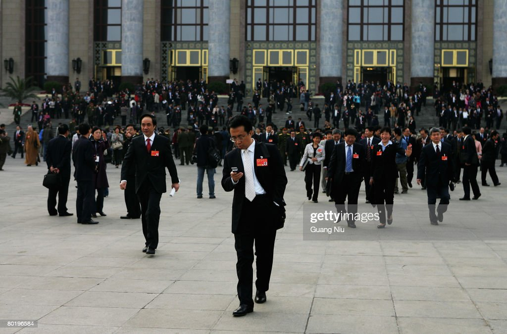 Delegates walk out of the Great Hall of the People after the fourth plenary session of the National People's Congress or parliament on March 11 2008...