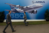 Delegates walk past a billboard of an A380 airliner outside one of the EADS company's chalets at the Farnborough Air Show The Airbus A380 is a...