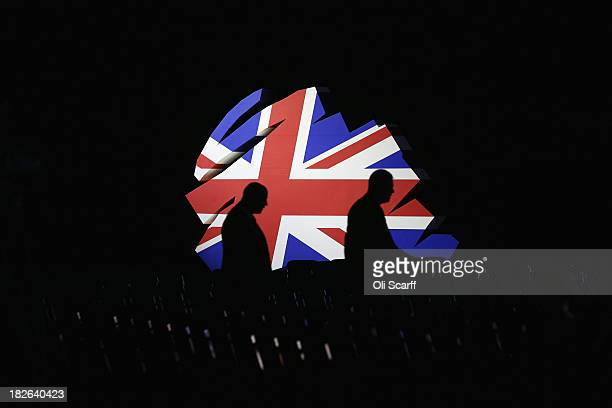 Delegates walk past a giant model of the Conservative Party logo before British Prime Minister David Cameron delivers his keynote speech to delegates...