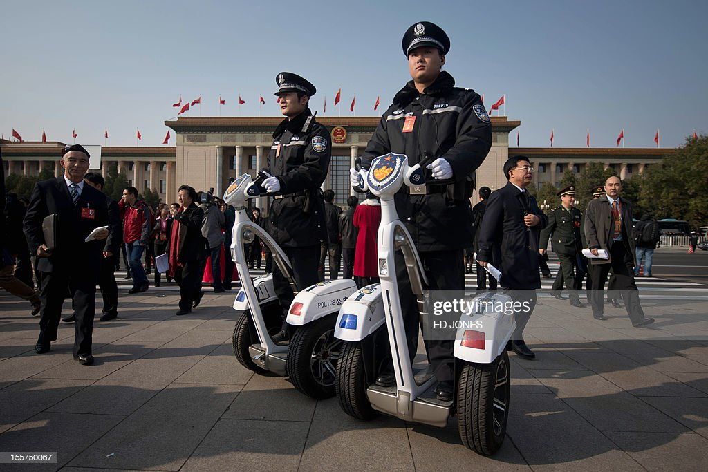 Delegates walk past policemen as they leave the opening session of the Chinese Communist Party's five-yearly Congress at the Great Hall of the People in Beijing on November 8, 2012. The week-long congress, held every five years, will end with a transition of power to Vice President Xi Jinping, who will govern for the coming decade amid growing pressure for reform of the communist regime's iron-clad grip on power. AFP PHOTO / Ed Jones