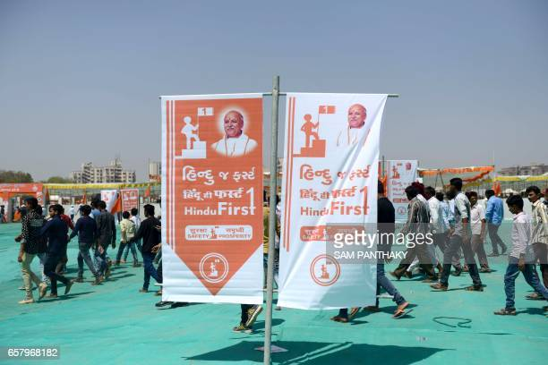 Delegates walk past signage as they arrive to attend a gathering of The Vishva Hindu Parishad at The GMDC grounds in Ahmedabad on March 26 which was...