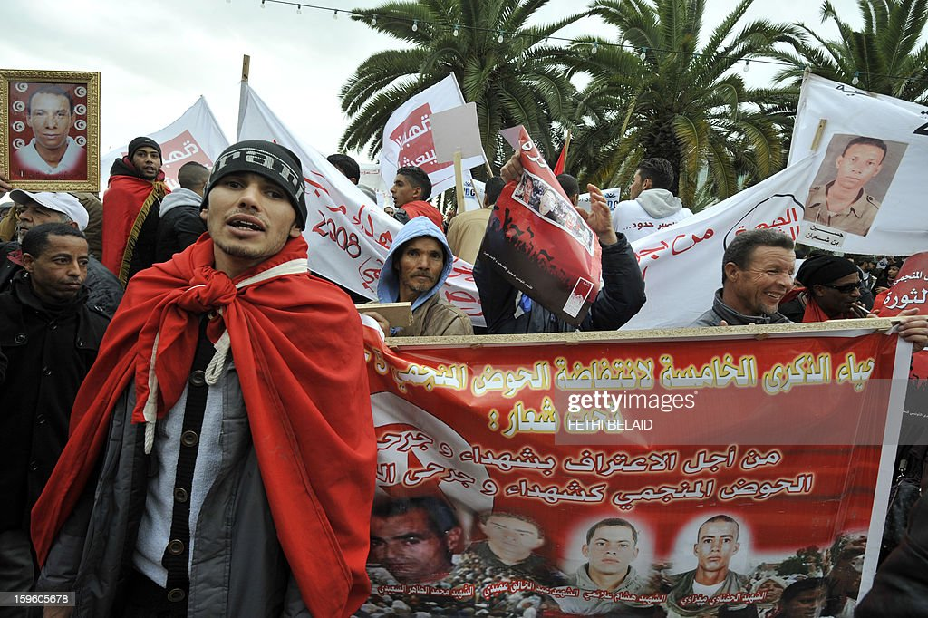 A delegation of people from Redeyef, in the Gafsa Mining Basin, hold banners and placards during a protest against the decision taken by the National Constituent Assembly (NCA) on January 17, 2013 outside the NCA building in Tunis. The NCA excluded two weeks ago the martyrs and wounded of the Revolution in 2008 from the decree-law 97 related to the compensation of the victims of the 2011 Revolution.