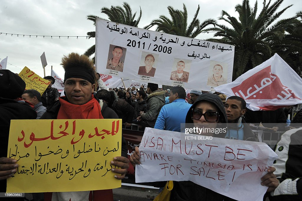 A delegation of people from Redeyef, in the Gafsa Mining Basin, hold pictures and placards during a protest against the decision taken by the National Constituent Assembly (NCA) on January 17, 2013 outside the NCA building in Tunis. The NCA excluded two weeks ago the martyrs and wounded of the Revolution in 2008 from the decree-law 97 related to the compensation of the victims of the 2011 Revolution.