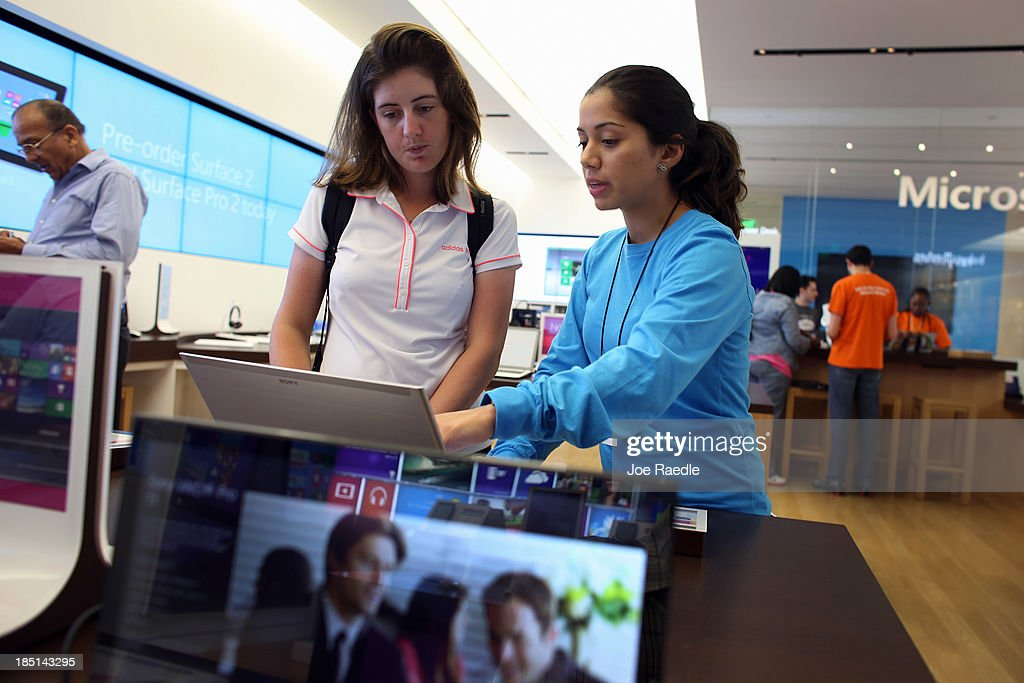 Delfina Acosta (L) is helped by Microsoft Product Advisor Daniela Belevanon as she shops for a computer loaded with the Windows 8.1 operating system at a Microsoft store in the Dadeland Mall October 17, 2013 in Miami, Florida. The update was released a year after Windows 8 was released and includes fixes to some of the problems people experienced with the initial release.