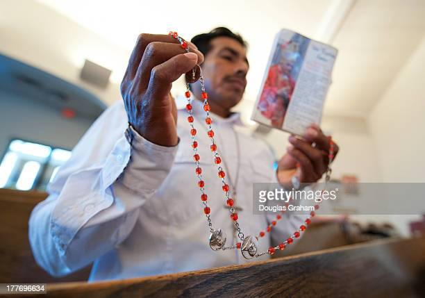 Delfino Velazquez holds his rosary beads as he prays with about 200 people who gathered for an emotional prayer vigil at Saint Paul Catholic Church...