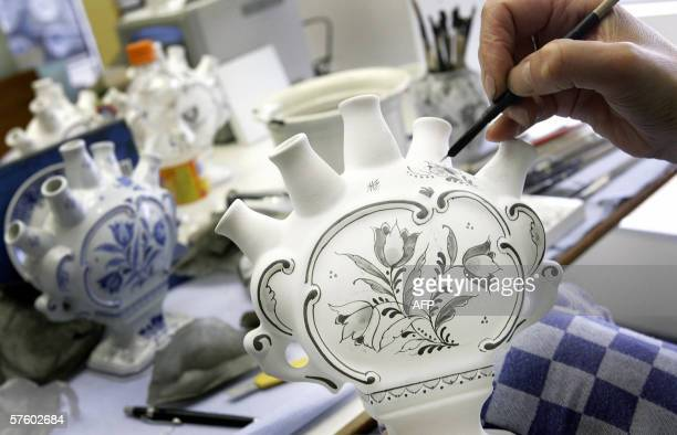 TO GO WITH AFP STORY 'NetherlandstourismartLifestyle' A painter decorates a tulip vase in delft blue style in the museum of the Koninklijke...