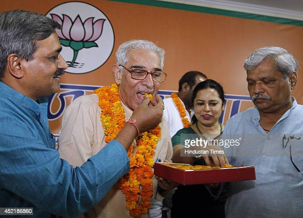Delhi BJP president Satish Upadhyay and vice president Prabhat Jha offering a sweets to veteran BJP leader OP Kohli during a function to felicitate...