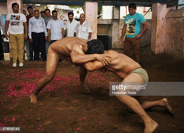 Delhi Chief Minister Arvind Kejriwal enjoying a friendly wrestling bout during his visit to Guru Hanuman Akhara on July 4 2015 in New Delhi India