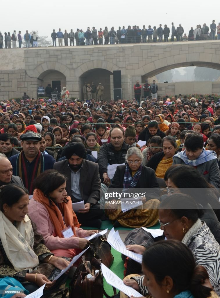 Delhi Chief Minister Sheila Dikshit (C) participates in a group prayer during the Women Dignity march in New Delhi on January 2, 2013. Several hundred people took part in the solidarity march for women organised by the Delhi government which ended at Rajghat, the memorial for slain independence hero Mahatma Gandhi. A gang of rapists who savagely assaulted a woman on a bus in New Delhi tried to run her over after the fatal attack, reports said January 2, citing a police account of the incident. AFP PHOTO/ Prakash SINGH