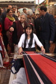 Delhi Chief Minister Sheila Dikshit watches as a woman weaves cloth on a traditional hand operated loom during the 25th Annual Dastkari Haat Craft...